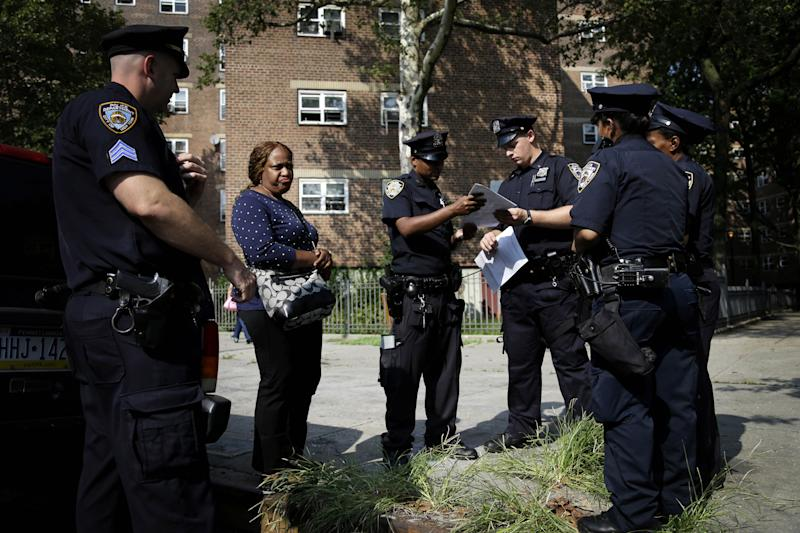 FILE - In this Aug. 13, 2013 file photo, police officers take a report from a woman who had her phone stolen in the Brownsville section in the Brooklyn borough of New York. Strategies that have dropped crime to record lows across the city haven't taken hold in the Brooklyn neighborhood of Brownsville, where the cycle of violence, silence and retribution seems entrenched. And community activists say a big police presence can't make up for better schools, more jobs and better housing. (AP Photo/Seth Wenig, File)