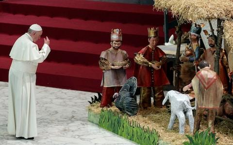 Pope Francis prays in front of a Nativity scene - Credit: Gregorio Borgia/AP