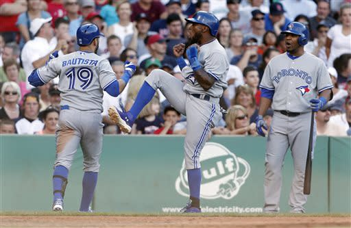 Toronto Blue Jays' Jose Bautista (19) celebrates his two-run home run that also drove in Jose Reyes, center, as Edwin Encarnacion, right, watches during the eighth inning of a baseball game against the Boston Red Sox in Boston, Saturday, June 29, 2013. (AP Photo/Michael Dwyer)