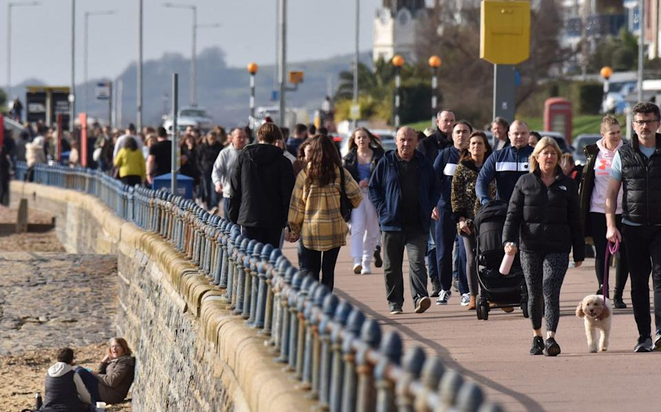 SOUTHEND, ENGLAND - FEBRUARY 21: People walk beside the beach on a warm sunny day as the weather warms for the week ahead on February 21, 2021 in Southend, England. Temperatures are predicted to rise to 18C for parts of the UK this week as a hot air plume is set to arrive from the Canary islands. After a surge of covid-19 cases, fueled partly by a more infectious variant of the virus, the British government had reimposed nationwide lockdown measures across England. A review was held on February 15 and despite deaths and infections falling, lockdown will continue. (Photo by John Keeble/Getty Images)