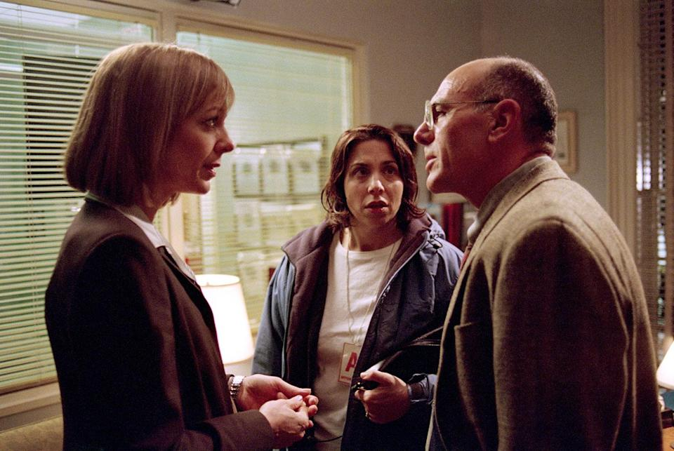 Allison Janney as C.J. talking with Carmen Argenziano as Leonard Wallace as Nancy Cassaro as Janet Price looks on. (© Warner Bros. Entertainment, Inc.)