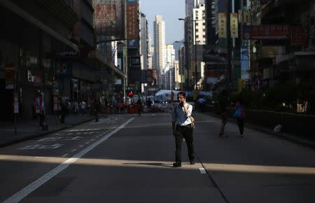 A man walks on a main road without traffic, after it was blocked by pro-democracy protesters, at Hong Kong's Mongkok shopping district October 7, 2014. REUTERS/Bobby Yip