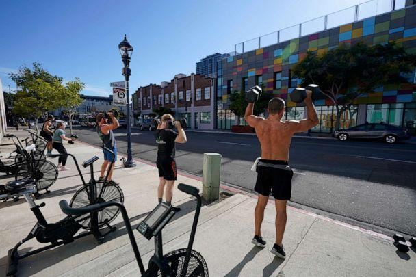 PHOTO: People lift weights outdoors while training at a gym in San Diego, Aug. 12, 2020. (Gregory Bull/AP, FILE)