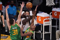 Los Angeles Lakers center Montrezl Harrell, center, shoots as Utah Jazz forward Georges Niang, left, and guard Trent Forrest defend during the first half of an NBA basketball game Saturday, April 17, 2021, in Los Angeles. (AP Photo/Mark J. Terrill)
