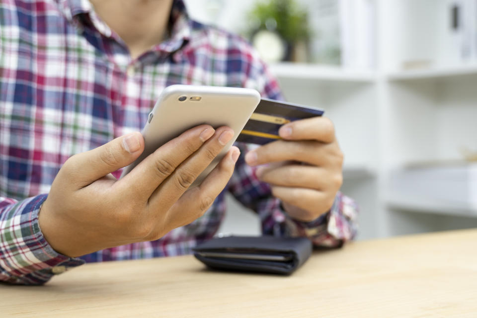 A stock image of a man using his credit card to pay for something on his phone. During the coronavirus pandemic, scammers have been using the virus and technology to scam Australians.