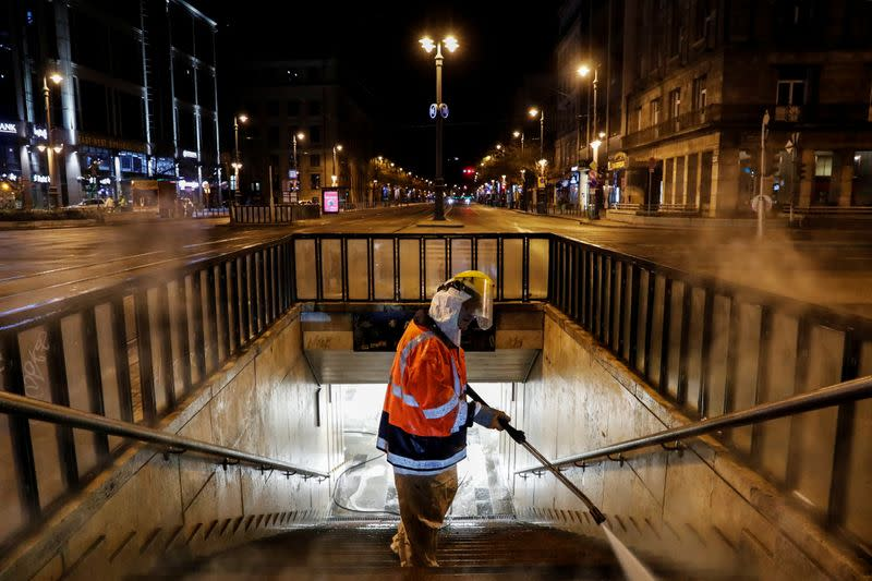 A worker wearing protective suit cleans and disinfects a flight of stairs of an underpass to prevent the spread of coronavirus disease (COVID-19), in downtown Budapest
