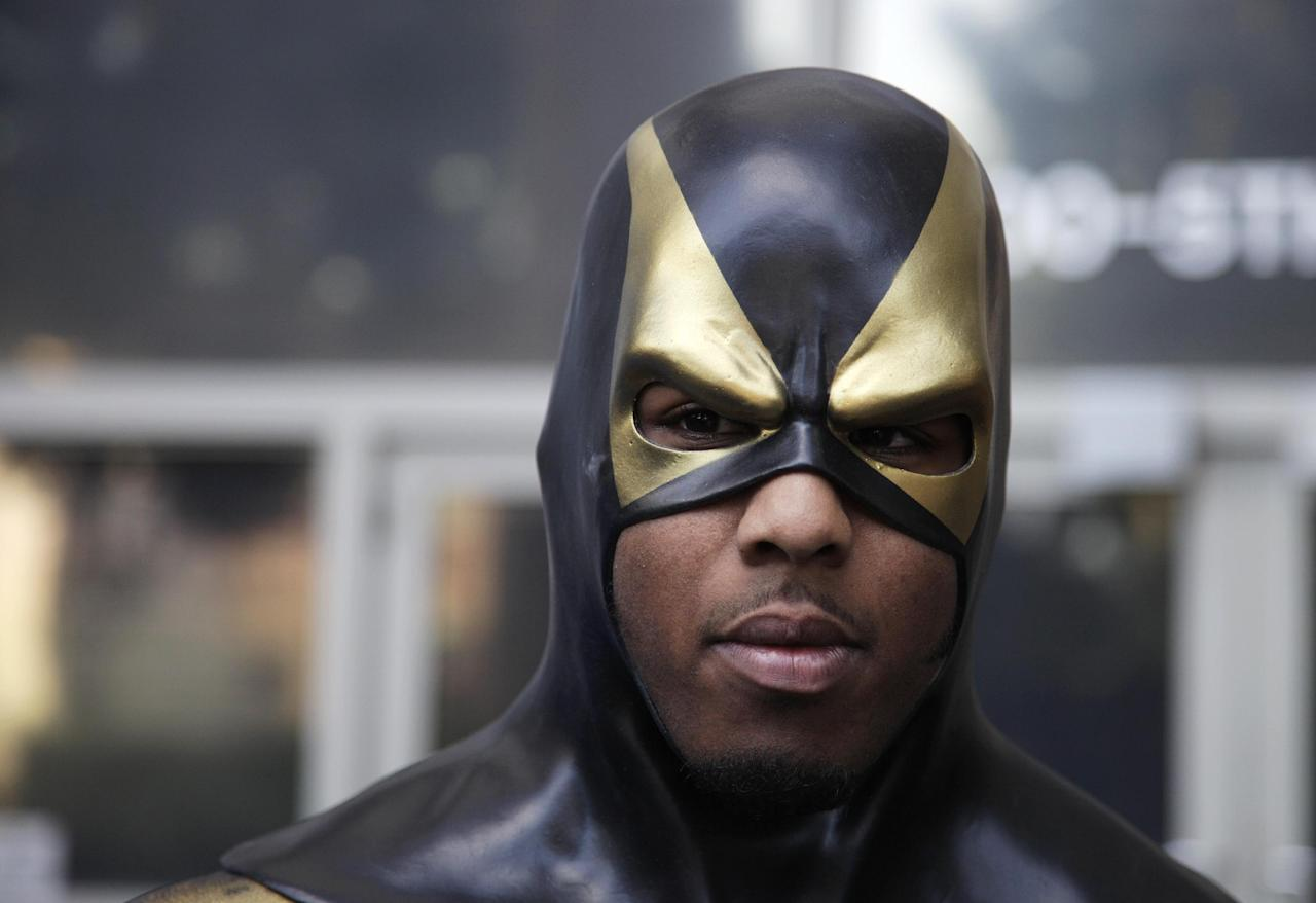 "FILE - In this Oct. 13, 2011 file photo, Benjamin Fodor, a self-styled superhero who goes by the name ""Phoenix Jones,"" wears his mask as he prepares to talk to reporters after he appeared in court in Seattle. As more people _ often, young people _ fashion themselves into superheroes, they risk finding themselves in similar situations where they wind up hurting innocent members of the public or being shot, stabbed or beaten themselves. (AP Photo/Ted S. Warren/file)"
