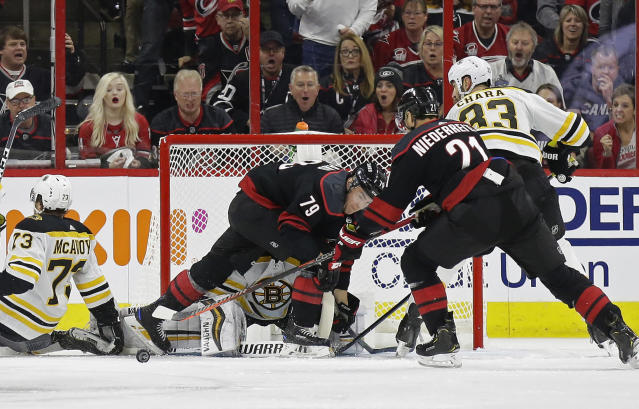 Carolina Hurricanes' Micheal Ferland (79) and Nino Niederreiter (21), of Switzerland, try to score against Boston Bruins goalie Tuukka Rask (40), of Finland, while Bruins' Zdeno Chara (33), of Slovakia, and Charlie McAvoy (73) defend during the first period in Game 3 of the NHL hockey Stanley Cup Eastern Conference final series in Raleigh, N.C., Tuesday, May 14, 2019. (AP Photo/Gerry Broome)