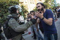 Israeli riot police tries to block a Jewish right-wing man as clashes erupted between Arabs, police and Jews, in the mixed town of Lod, central Israel, Wednesday, May 12, 2021. As rockets from Gaza streaked overhead, Arabs and Jews fought each other on the streets below. Rioters torched vehicles, a restaurant and a synagogue in one of the worst spasms of communal violence that Israel has seen in years. (AP Photo/Heidi Levine)