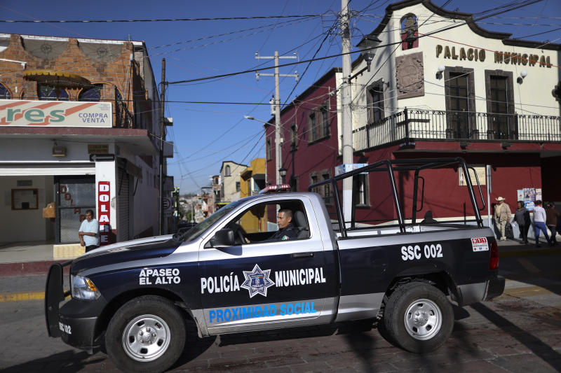In this Feb. 10, 2020 photo, a policeman drives past town hall in Apaseo El Alto, Guanajuato state, Mexico. Part of Guanajuato's odd reality stems from its success at cracking down on crimes that impact businesses together with its inability to stop the drug gang war. In 2019, 79 police officers were killed in the state. (AP Photo/Rebecca Blackwell)