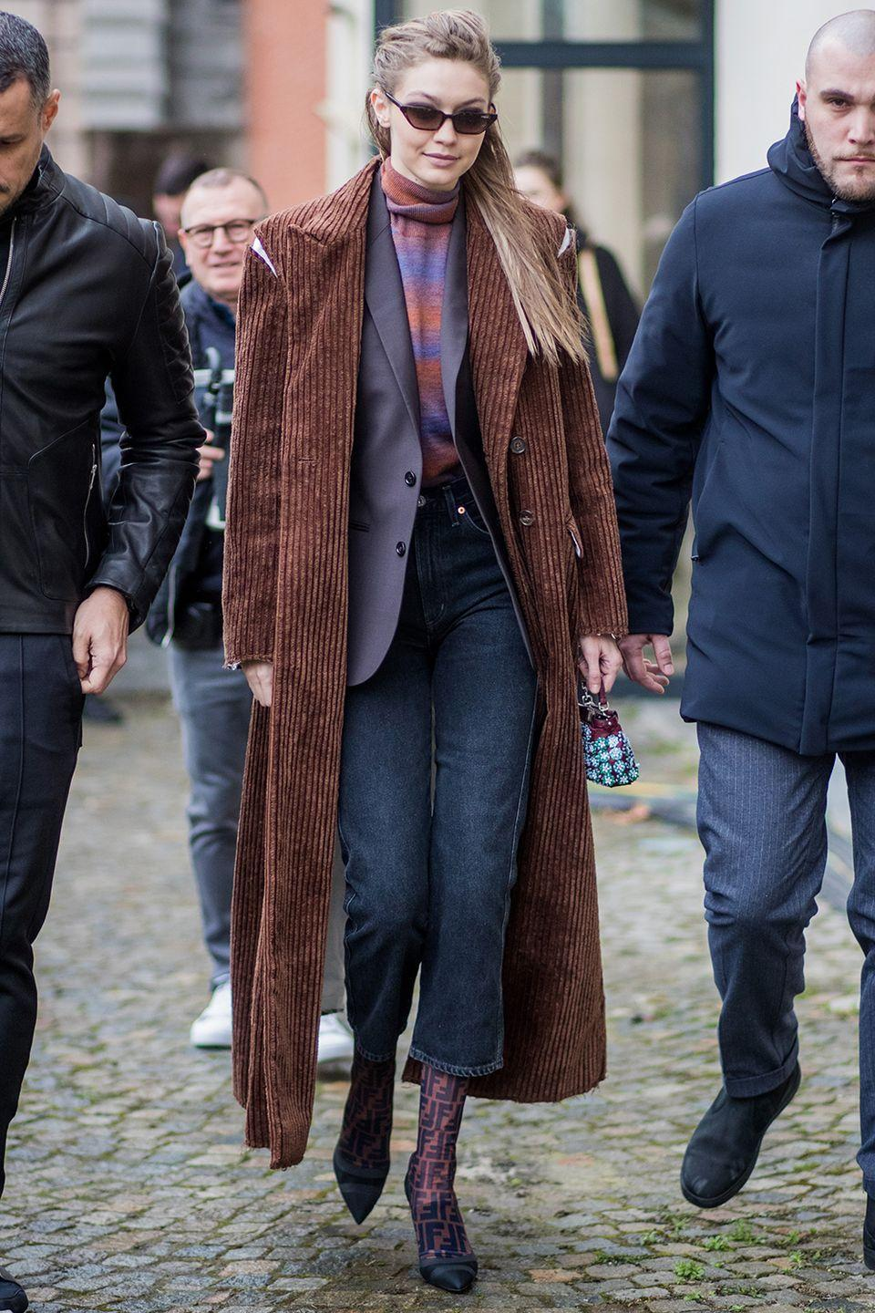 <p>In a Christian Dada corduroy double-breasted overcoat with subtle split shoulders detail, over a deep plum Paul & Joeblazer, over a red and purple striped turtleneck, finished with Fendi mesh monogram boots tucked under cropped jeans, a tiny micro purse, and small cat-eye sunglasses while out in Milan.</p>