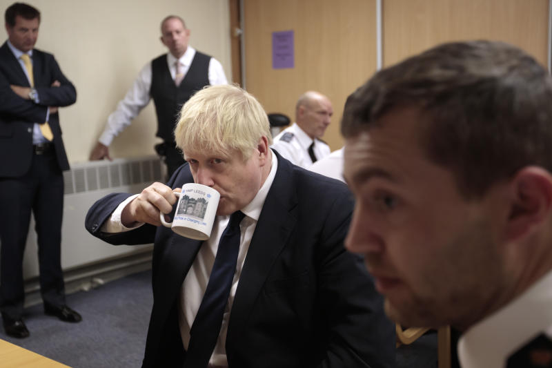 Britain's Prime Minister Boris Johnson takes a drink from a prison mug as he talks with prison staff during a visit to Leeds prison, Northern England Tuesday Aug. 13, 2019. In an announcement on Sunday Johnson promised more prisons and stronger police powers in an effort to fight violent crime. (AP Photo/Jon Super)