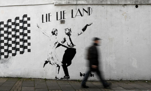 <p>A pedestrian passes a new piece of art by street artist Bambi in London. in London, eb. 16, 2017. The work, entitled Lie Lie Land, features a dancing British Prime Minister Theresa May and President Donald Trump in the pose made famous by the movie La La Land. (Photo: Kirsty Wigglesworth/AP) </p>