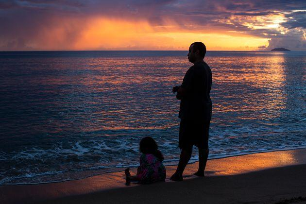 People observe the sunset at Los Almendros beach in Rincón, Puerto Rico, on Aug. 2. (Photo: Erika P. Rodriguez for HuffPost)