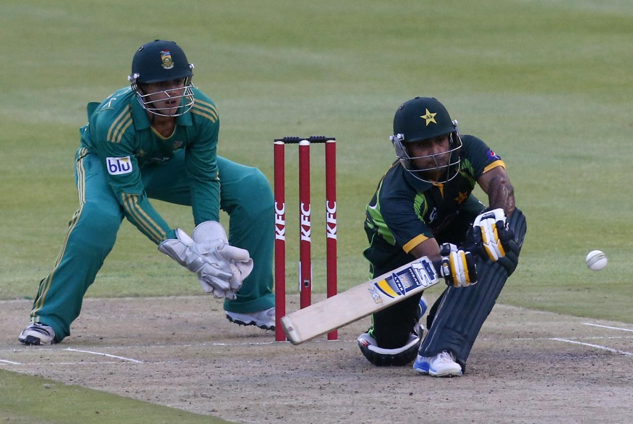 Pakistan's Mohammad Hafeez plays a shot during the second Twenty20 cricket match against South Africa in Cape Town, November 22, 2013. Looking on is South Africa's AB de Villiers. REUTERS/Mike Hutchings (SOUTH AFRICA - Tags: SPORT CRICKET)