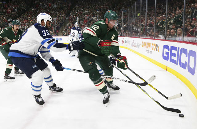 Minnesota Wild center Eric Staal (12) controls the puck in front of Winnipeg Jets defenseman Dustin Byfuglien (33) in the first period of an NHL hockey game on Sunday, April 15, 2018, in St. Paul, Minn. (AP Photo/Andy Clayton-King)