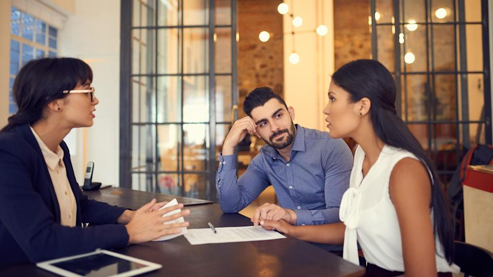 Shot of a young couple meeting with a financial planner in an office.