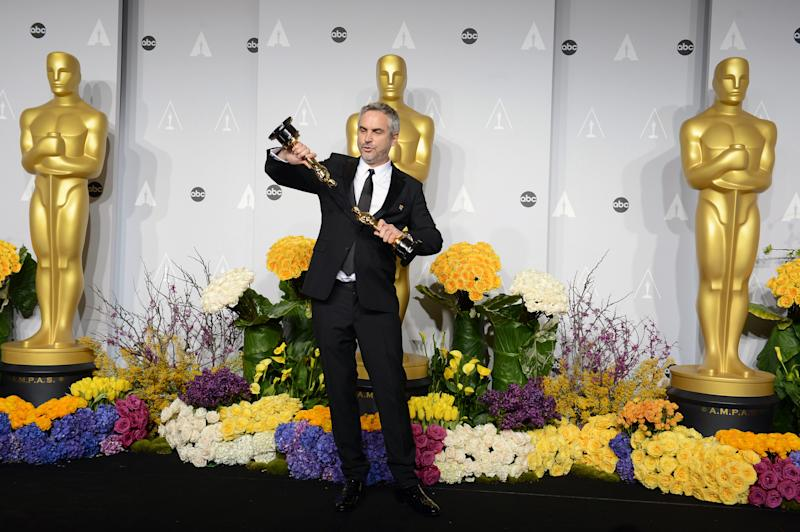 """Alfonso Cuaron poses in the press room with his awards for best film editing and best director for """"Gravity"""" during the Oscars at the Dolby Theatre on Sunday, March 2, 2014, in Los Angeles. (Photo by Jordan Strauss/Invision/AP)"""