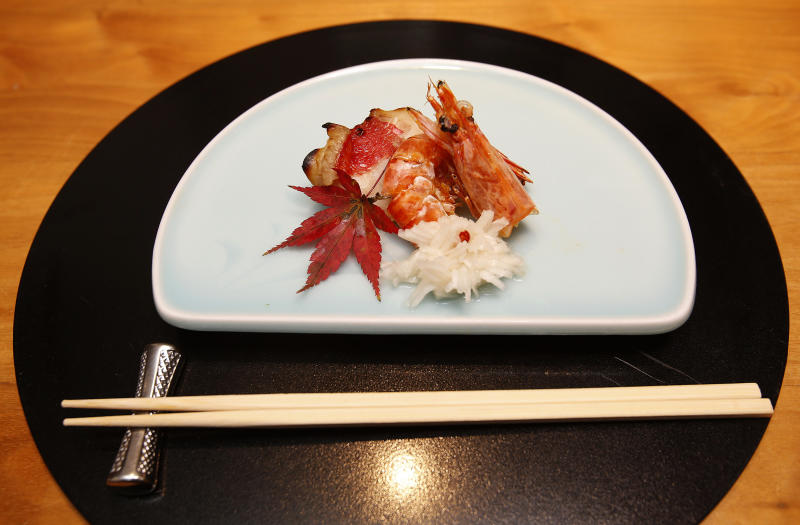 In this Wednesday, Nov. 27, 2013 photo, a dish of crab and shrimp with vinegared turnip are served on a table at Japanese restaurant Irimoya Bettei in Tokyo. Washoku, the traditional cuisine of Japan, is being considered for designation as part of the world's priceless cultural heritage by the U.N. this week. But even as sushi and sake booms worldwide, purists say its finer points are candidates for the endangered list at home. The younger generation is increasingly eating Krispy Kreme donuts and McDonald's, not rice. (AP Photo/Shizuo Kambayashi)