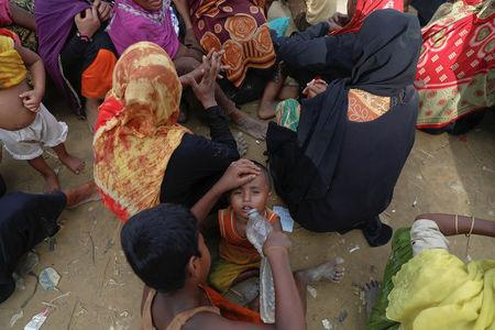 Rohingya refugees wait for humanitarian aid to be distributed at a camp for those who recently fled from Myanmar, near Cox's Bazar