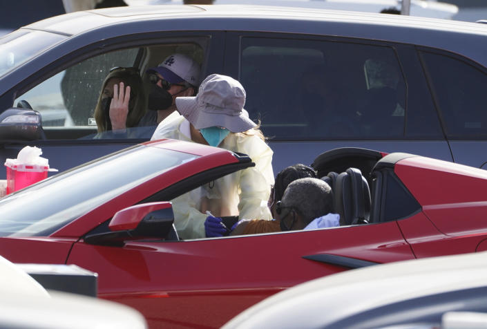 A woman is vaccinated inside a convertible vehicle at a mass COVID-19 vaccination site outside The Forum in Inglewood, Calif., Tuesday, Jan. 19, 2021. California has become the first state to record more than 3 million known coronavirus infections. That's according to a tally Monday by Johns Hopkins University. (AP Photo/Damian Dovarganes)