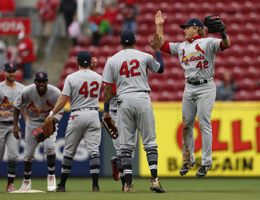 St. Louis Cardinals' Harrison Bader, front right, and Jose Martinez, front left, celebrate their 3-2 win over the Cincinnati Reds in a baseball game, Sunday, April 15, 2018, in Cincinnati. (AP Photo/Gary Landers)