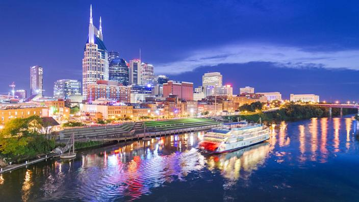 Nashville, Tennessee, USA skyline and riverboat on the Cumberland River at night.