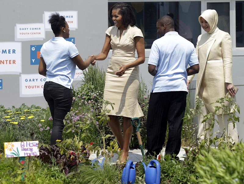 First lady Michelle Obama and Hayrunnisa Gul, right, wife of Turkish President Abdullah Gul visit with students in the rooftop garden while touring the Gary Comer Youth Center with the spouses of  NATO leaders, Sunday, May 20, 2012, on the South Side of Chicago. The Center offers young people diverse, educational and extracurricular enrichment activities as well as support to help prepare them to graduate from high school and to pursue college and meaningful careers.(AP Photo/M. Spencer Green)