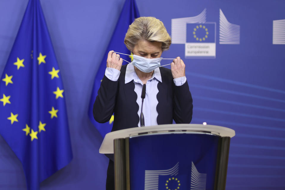 FILE - In this Nov. 16, 2020, file photo, European Commission President Ursula von der Leyen removes her face mask as she arrives to give a statement at the EU headquarters in Brussels. The European Union still hasn't completely sorted out its messy post-divorce relationship with Britain — but it has already been plunged into another major crisis. This time the 27-member union is being tested as Poland and Hungary block passage of its budget for the next seven years and an ambitious package aimed at rescuing economies ravaged by the coronavirus pandemic. (Kenzo Tribouillard, Pool Photo via AP, File)