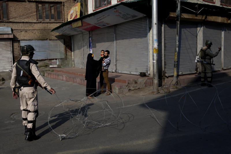 A Kashmiri family waits for a lift to take their sick child to hospital as Indian paramilitary soldiers stand guard near a checkpoint during lockdown in Srinagar, Indian controlled Kashmir, Friday, Aug. 23, 2019. The latest crackdown began just before Prime Minister Narendra Modi's Hindu nationalist-led government stripped Jammu and Kashmir of its semi-autonomy and its statehood, creating two federal territories. (AP Photo/Dar Yasin)