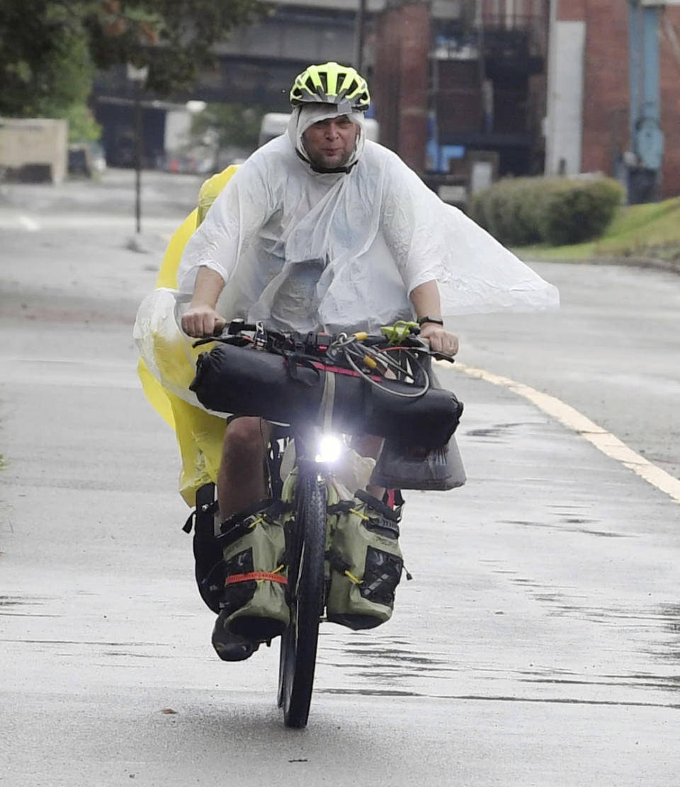 With the rain falling, a bicyclist dressed in wet weather gear travels along the Great Allegheny Passage near the McKeesport Hostel Tuesday, Aug. 31, 2021, in McKeesport, Pa. (Nate Guidry/Pittsburgh Post-Gazette via AP)