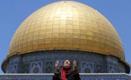 Palestinian woman prays in front of the Dome of the Rock on the first Friday of the holy month of Ramadan at the compound known to Muslims as the Noble Sanctuary and to Jews as Temple Mount, in Jerusalem's Old City June 19, 2015. REUTERS/Ammar Awad/Files