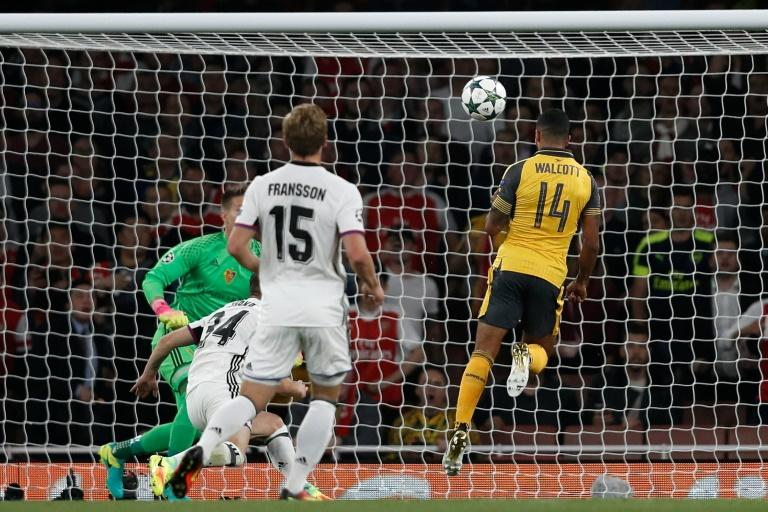 Arsenal's midfielder Theo Walcott (R) heads the opening goal past Basel's goalkeeper Tomas Vaclik (L) during the UEFA Champions League Group A football match between Arsenal and FC Basel at The Emirates Stadium in London