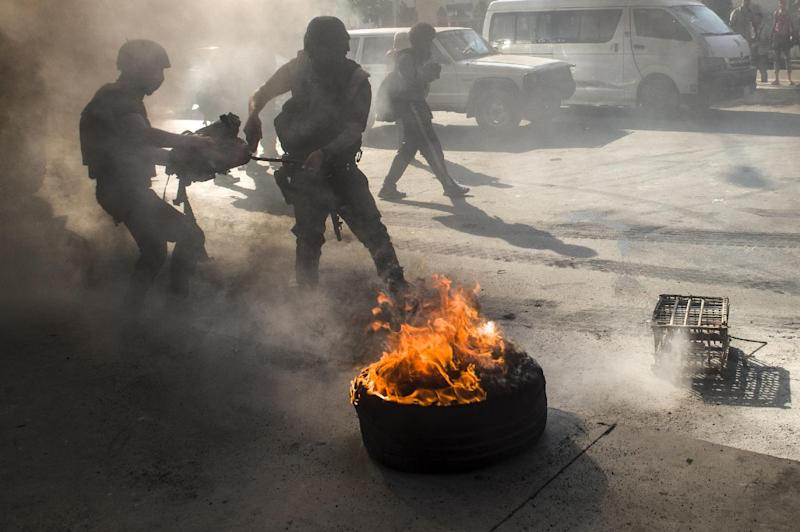 Egyptian riot policemen douse burning tyres during a rally to mark the first anniversary of the military ouster of president Mohamed Morsi on July 3, 2014 in Cairo