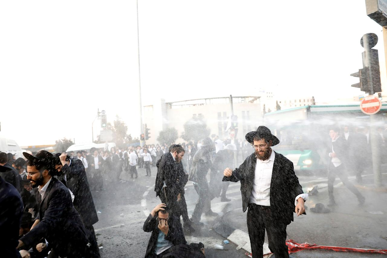 Ultra-Orthodox Jewish men get sprayed by the police while trying to block a road during a protest in Jerusalem, October 23, 2017. REUTERS/Ronen Zvulun