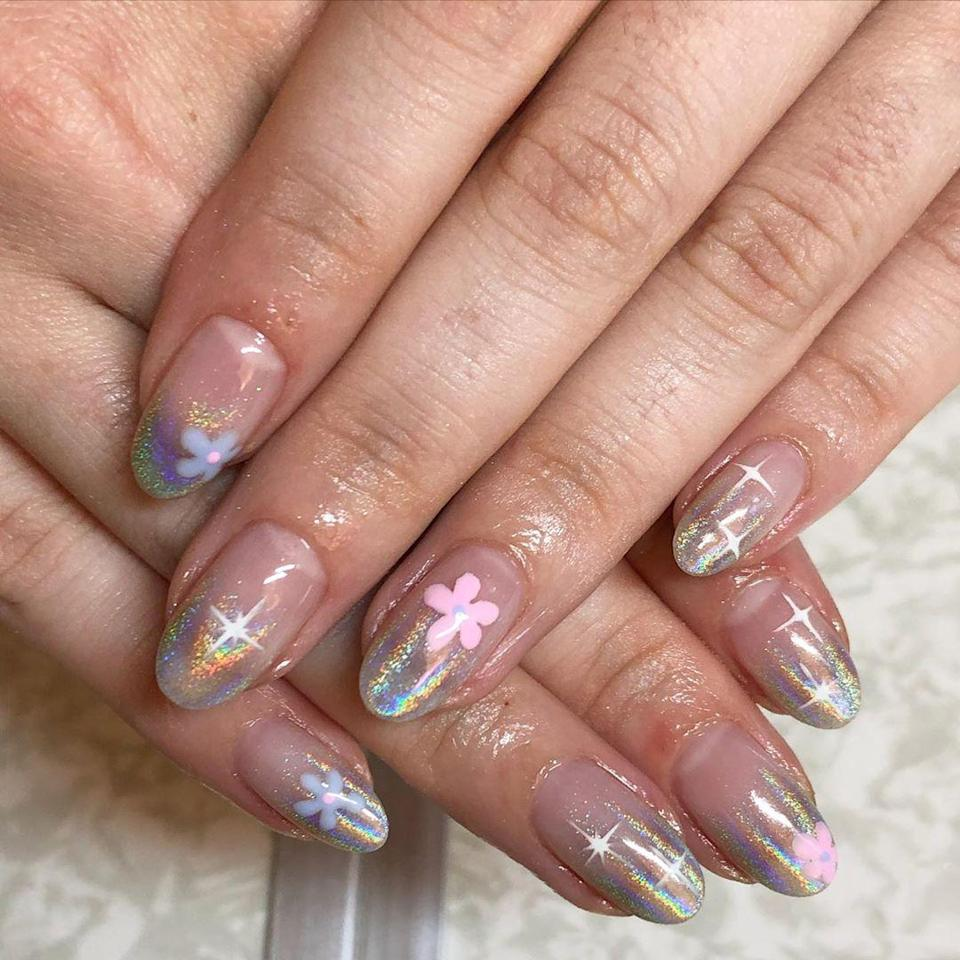 These holographic tips and pastel flowers look like they jumped out of an episode of Sailor Moon. Add to the anime vibes with the cartoon sparkle effects. So cute.