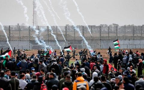 <span>Tear gas canisters fall amongst Palestinian protesters during the demonstration</span> <span>Credit: &nbsp;MAHMUD HAMS/AFP </span>