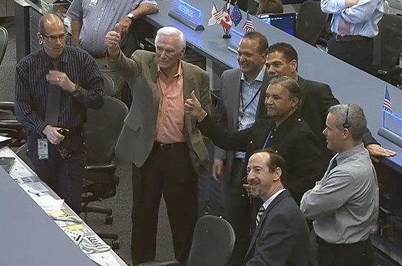 Apollo 17 moonwalker Gene Cernan (left) gives a thumbs up to the astronauts on the International Space Station from Mission Control in Houston on Tuesday, Feb. 5, 2013.