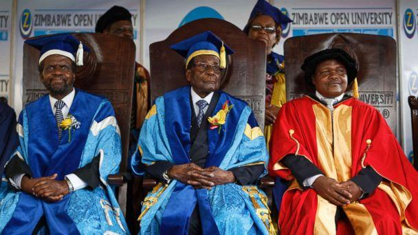 PHOTO: Zimbabwe's President Robert Mugabe, center, sits for formal photographs with university officials, after presiding over a student graduation ceremony at Zimbabwe Open University on the outskirts of Harare, Zimbabwe, Nov. 17, 2017. (Ben Curtis/AP)