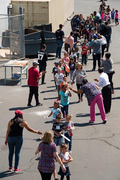 Children are on their way to be reunited with parents after a gunman entered a classroom and killed one woman and one student, before turning the gun on himself, at North Park Elementary School in San Bernardino, California, April 10 2017 (AFP Photo/Robyn Beck)