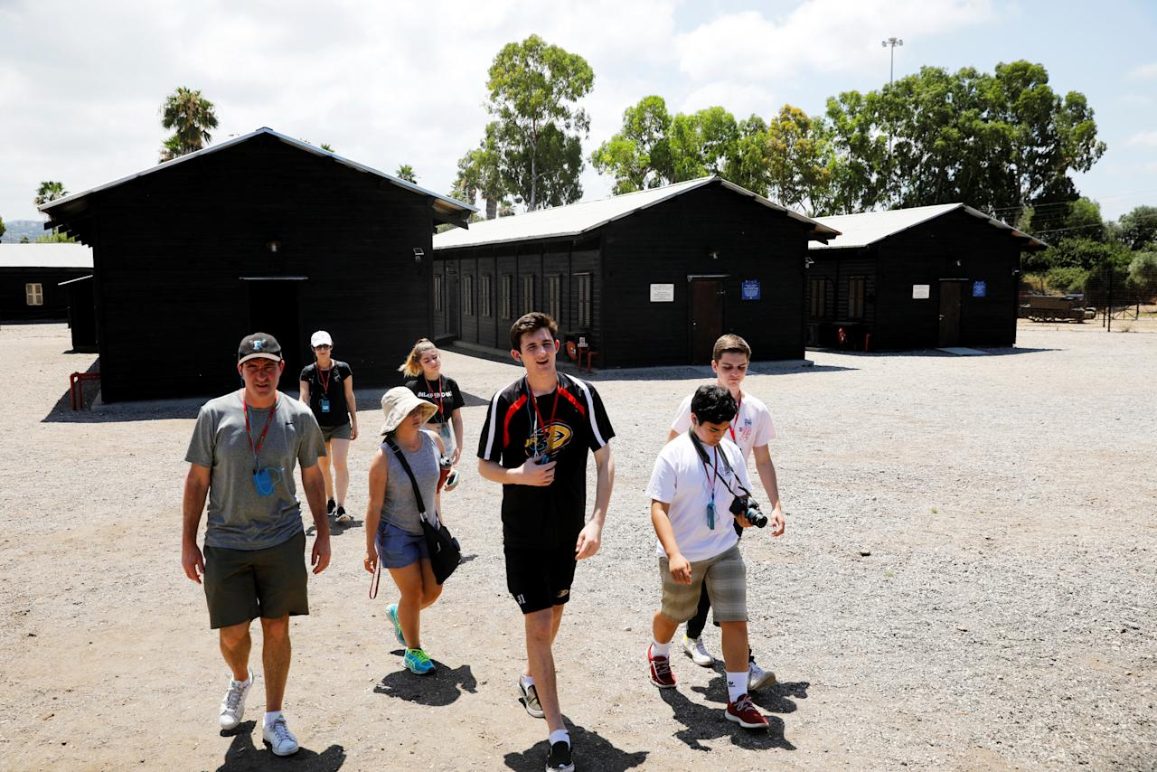 Tourists walk next to huts in which illegal Jewish immigrants were detained, at the former British detention camp of Atlit, currently operated as a museum by the Council for Conservation of Heritage Sites in Israel, June 19, 2018. Picture taken June 19, 2018. REUTERS/Amir Cohen