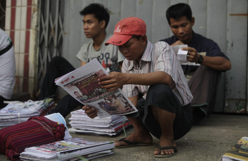 A Myanmar newspaper hawker reads a newspaper featuring pro-democracy leader Aung San Suu Kyi a day after landmark by-elections in Yangon, Myanmar, Monday, April 2, 2012. Suu Kyi, 66, was elected to parliament Sunday in a historic victory buffeted by the jubilant cheers of supporters who hope her triumph will mark a major turning point in a nation still emerging from a ruthless era of military rule. (AP Photo/Altaf Qadri)