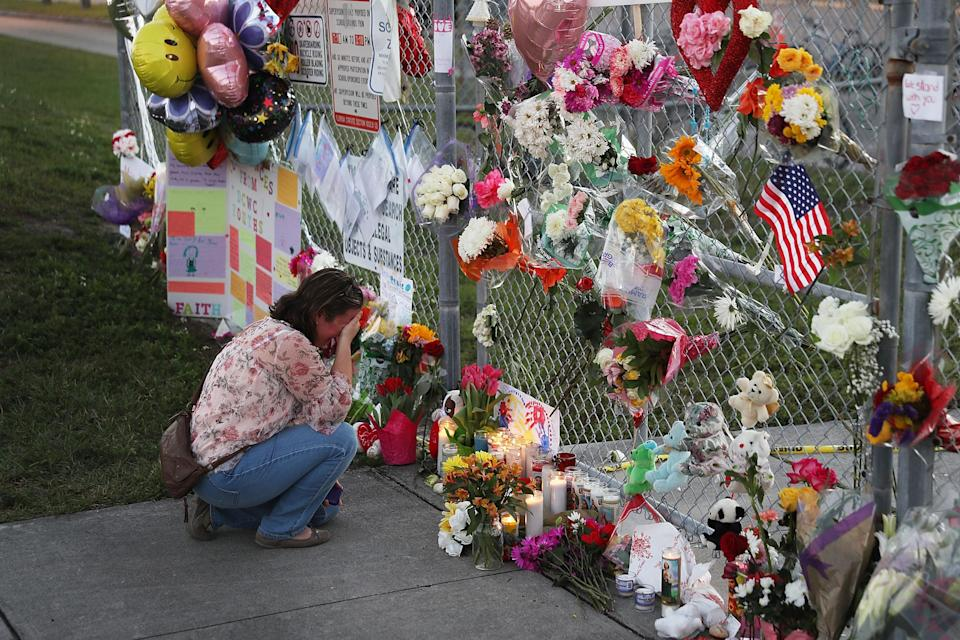 A mourner observes flowers left at the scene of the Florida high school massacre last week. (AFP/Getty)