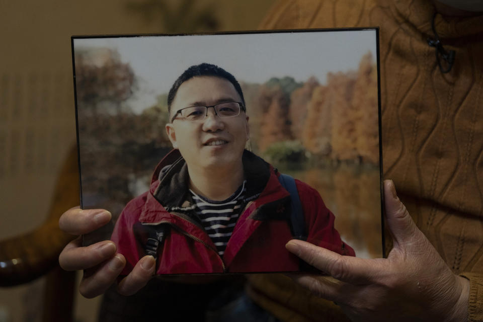 Zhong Hanneng holds a photo of her son, Peng Yi, and talks about his difficulties in getting tested for COVID-19, eventually dying from the disease, in Wuhan in central China's Hubei province on Saturday, Oct. 17, 2020. Widespread test shortages and problems at a time when the coronavirus arguably could have been curbed were caused largely by secrecy and cronyism at China's top disease control agency, an Associated Press investigation has found. (AP Photo/Ng Han Guan)