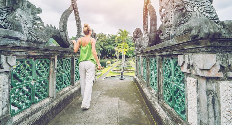 A young woman visits Bali's Tirta Gangga temple. Indonesian Authorities could soon ban tourists from visiting temples unaccompanied.