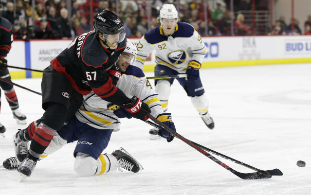 Carolina Hurricanes' Trevor van Riemsdyk (57) and Buffalo Sabres' Conor Sheary chase the puck during the second period of an NHL hockey game in Raleigh, N.C., Saturday, March 16, 2019. (AP Photo/Gerry Broome)