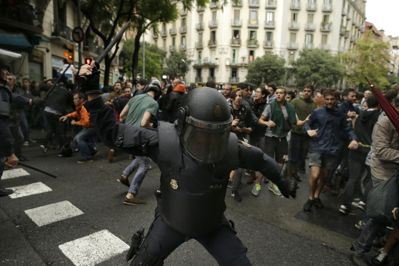 <p>Spanish riot police swings a club against would-be voters near a school assigned to be a polling station by the Catalan government in Barcelona, Spain, Oct. 1, 2017. Spanish riot police have forcefully removed a few hundred would-be voters from several polling stations in Barcelona. (Photo: Manu Fernandez/AP) </p>