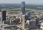 FILE - In this May 15, 2014 file photo, the Devon Energy Tower dwarfs other downtown buildings in Oklahoma City. The U.S. Department of Justice announced Monday, Sept. 27, 2021, that Oklahoma City-based Devon Energy Corporation and its affiliates have agreed to a $6.15 million settlement agreement with the federal government over allegations it underpaid royalties on federal leases. (AP Photo/Sue Ogrocki, File)