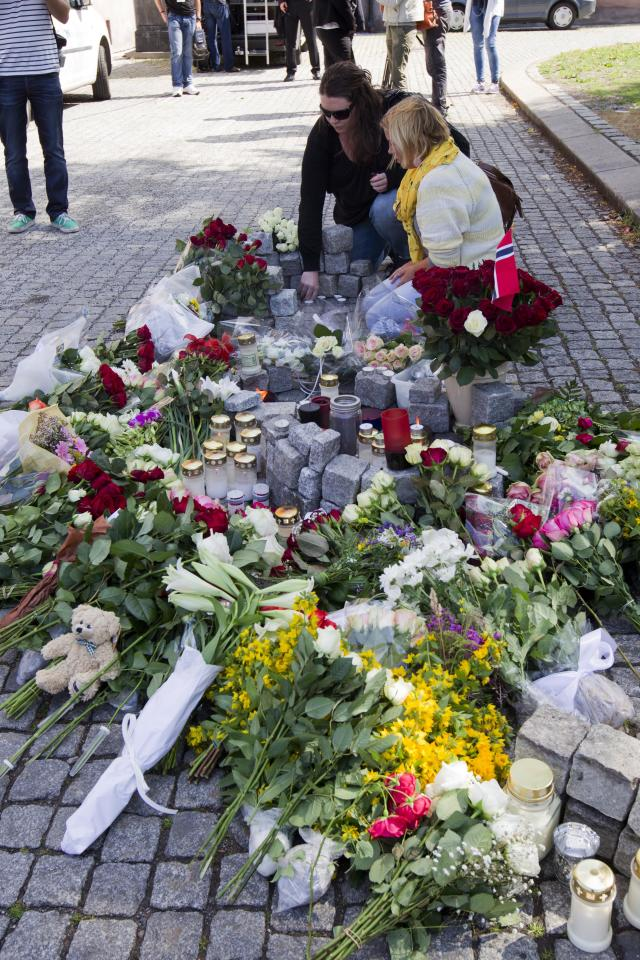 Flowers are laid down outside Oslo Cathedral, Oslo Saturday July 23, 2011, in memory of the victims of Friday's twin attack in Oslo and island of Utoya. A Norwegian gunman disguised as a police officer beckoned his victims closer before shooting them one by one, claiming at least 84 lives, in a horrific killing spree on an idyllic island teeming with youths that has left this peaceful Nordic nation in mourning. The island tragedy Friday unfolded hours after a massive explosion ripped through a high-rise building housing the prime minister's office, killing seven people.(AP Photo/Scanpix/Berit Roald)