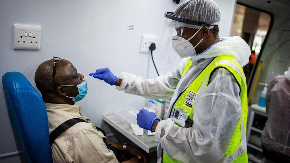 A medical staff member of the South Africa Health Department obtains a nasal swab sample from a passenger in a mobile testing unit at O.R Tambo International Airport in Ekurhuleni on December 30, 3030, where passengers that have COVID-19 symptoms upon arrival are tested. (Photo by Luca Sola / AFP) (Photo by LUCA SOLA/AFP via Getty Images)
